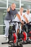 Senior man on spinning bike holding Royalty Free Stock Images