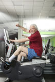 Senior man spinning on fitness bike in gym Royalty Free Stock Images