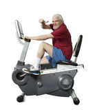 Senior man spinning on fitness bike isolated Royalty Free Stock Photography