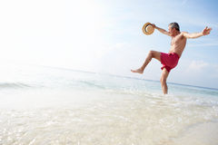Senior Man Splashing In Sea On Beach Holiday Stock Photography