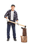 Senior man splitting a log with an axe Stock Photos