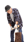 Senior man splitting a log with an axe Royalty Free Stock Photography