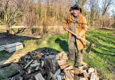 Senior man splitting wood with ax in the garden. Senior man splitting wood with ax in the autumn garden Stock Images