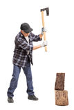 Senior man splitting wood with a hand axe Stock Photography