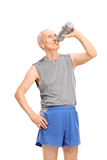 Senior man in sportswear drinking water. Vertical shot of a active senior man in sportswear drinking water from a bottle  on white background Stock Images