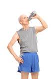 Senior man in sportswear drinking water Stock Images