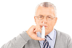 Senior man spraying medication in his nose Royalty Free Stock Photo
