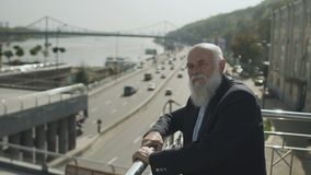 Senior man stand on observation deck and enjoys a view on a urban road and river. Old gray-haired man wearing suit is outdoors. Intelligent elderly man stands at stock video