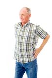 Senior man standing with arms akimbo and thinking Royalty Free Stock Image