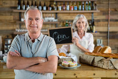 Senior man standing with arms crossed while woman holding open signboard. In caf Stock Photos