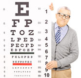 Senior man standing behind eyesight test. Isolated on white background, shot with a tilt and shift lens Royalty Free Stock Photos