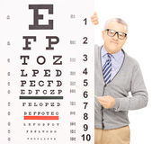 Senior man standing behind eyesight test and pointing with a sti Royalty Free Stock Image