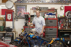 Senior man standing behind motorcycle in automobile repair shop Royalty Free Stock Image