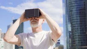 Senior man standing in business district using virtual reality glasses. Skyscrapers on background stock video footage