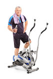 Senior man standing on a cross trainer machine. Senior man holding a water bottle and standing on a cross trainer machine  on white background Royalty Free Stock Images