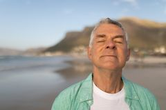 Senior man standing with eyes closed on the beach. Close up of active senior man standing with eyes closed on the beach stock photos