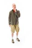 Senior man standing with finger on lips Stock Image