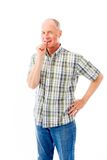 Senior man standing with finger in mouth Royalty Free Stock Photo