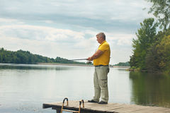 Senior man standing and fishing on the dock Stock Photos