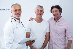 Senior man standing with guardian in hospital. Portrait of senior men standing with guardian in hospital Royalty Free Stock Photography