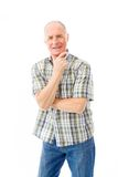 Senior man standing with hand on chin Stock Photo