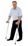 Senior man standing with the help of crutches. Recovering from an accident Stock Photos