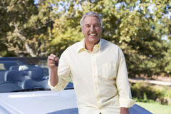 A senior man standing by his car Stock Images