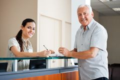 Senior Man Standing At Hospital Reception. Portrait of senior men standing at hospital reception while female making an entry in book Stock Photos