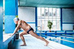 Senior man stretching by the indoor swimming pool. royalty free stock image