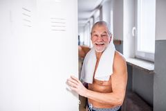 Senior man standing by the lockers in an indoor swimming pool. stock image