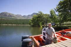 Senior man standing in motorboat beside lake jetty, tying rope to mooring post, smiling, portrait Royalty Free Stock Images