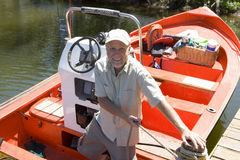 Senior man standing in motorboat beside lake jetty, tying rope to mooring post, smiling, portrait Stock Photography