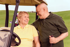 Senior man standing near his wife in cart. Soft glance. Smiling senior men with golf club standing near his wife sitting in cart and gently hugging her Stock Images