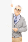 Senior man standing next to blank panel and holding a stick Stock Photos