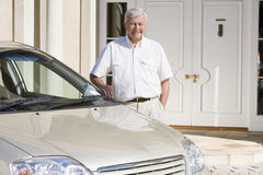 Senior man standing next to new car Stock Images