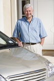 Senior man standing next to new car Royalty Free Stock Image
