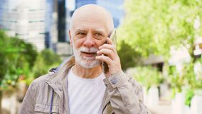 Senior man standing outdoors using smartphone. Downtown business district on background. Bearded senior man standing outdoors using cellphone. Retired male stock video footage