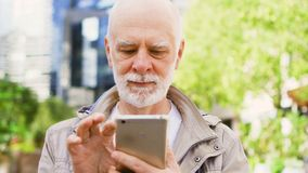 Senior man standing outdoors using smartphone. Downtown business district on background. Bearded senior man standing outdoors using cellphone. Retired male stock footage