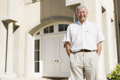Senior man standing outside house Stock Images