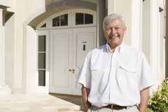 Senior man standing outside house Royalty Free Stock Photo
