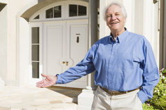 Senior man standing outside house Royalty Free Stock Images