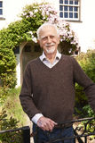 Senior Man Standing Outside Pretty Cottage Royalty Free Stock Photography