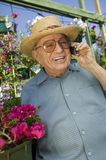 Senior Man standing in plant nursery Using Cell Phone Royalty Free Stock Photography