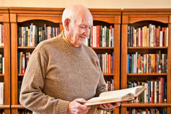 Senior Man Standing and Reading Book in Library. Upper half of senior male in a light brown sweater standing sideways and holding and reading a book. Blurred Stock Photo