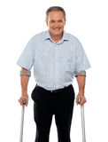 Senior man standing with support of crutches. Isolated against white background Stock Photos