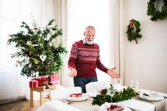 A senior man standing by a table set for a dinner at home at Christmas time. A surprised senior man standing by a table set for a dinner at home at Christmas royalty free stock images