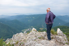 Senior man standing on top of a mountain