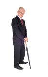 Senior man standing with umbrella. A senior man in a dark suit and tie standing isolated for white background Stock Photography