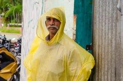 Senior man standing  under rain wearing raincoat Royalty Free Stock Photo
