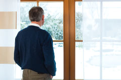 Senior man standing at the window looking out Royalty Free Stock Photography
